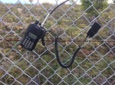 Icom V85 clipped onto the chain fence